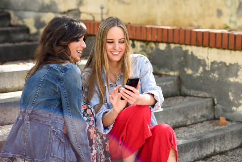two-women-sharing-social-media-with-smart-phone-CWJQ3T2-1030x687 Facebook Ads Explained in 400 Words or Less  - Clear Partnering Group - Orthodontic and Dental Marketing