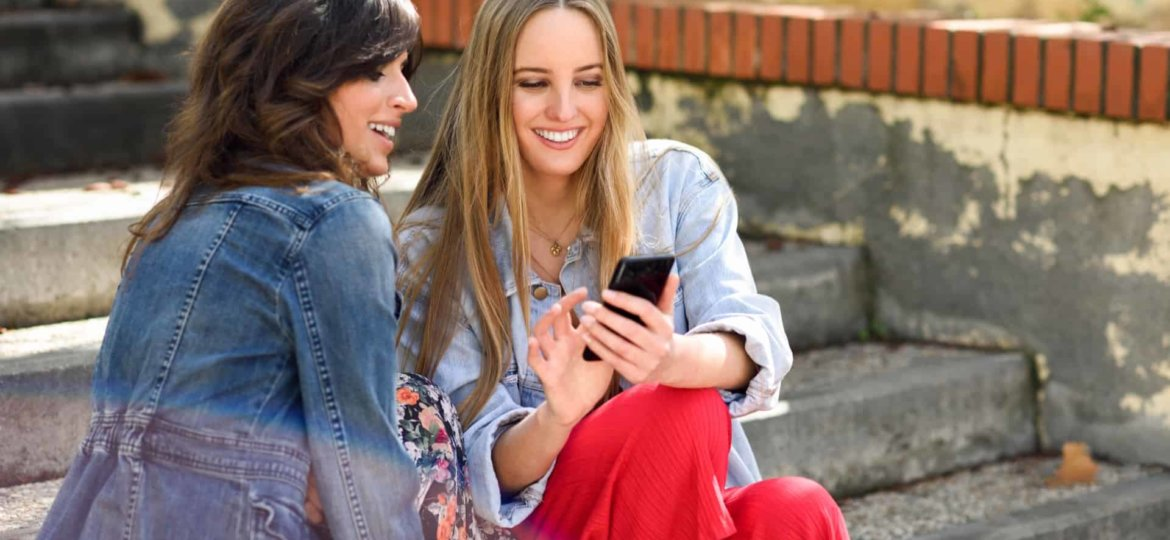 Two women sharing social media with smart phone outdoors